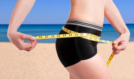 Diet Time. Woman measuring her waist with a yellow measuring tape. Beach background Stock Photo