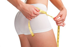 Diet Time. Woman measuring her waist with a yellow measuring tape Royalty Free Stock Image