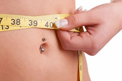 Diet Time. Closeup of a woman measuring her waist with a yellow measuring tape, isolated in white Stock Photos