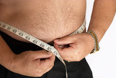 Diet time. An overweight caucasian male with a tape measure Royalty Free Stock Image