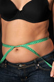 Diet time. Fat woman holding a measurement tape against blackbackground Royalty Free Stock Photography