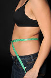 Diet time. Fat woman holding a measurement tape against blackbackground Stock Photo