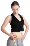 Diet Time. Woman measuring her waist with a yellow measuring tape, isolated in white Stock Photos