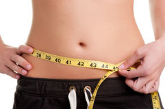 Diet Time. Woman measuring her waist with a yellow measuring tape, isolated in white Royalty Free Stock Photos
