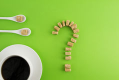 Diet, unhealthy sweet addiction concept. White cup of coffee or tea, two spoons and brown sugar cubes as question mark Royalty Free Stock Images