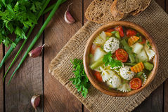 Diet vegetable soup with chicken meatballs and fresh herbs in wooden bowl, top view. Royalty Free Stock Images