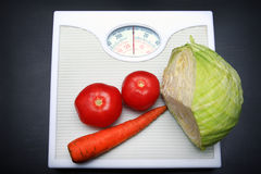 Diet. Vegetables lies on scales and symbolizes healthy food stock photos