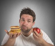 Diet vs junk food. Man undecided between diet and junk food Royalty Free Stock Photo