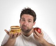 Diet vs junk food. Man undecided between diet and junk food Stock Image