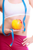 Diet. Waist of fitness woman fit girl with measure tape and apple Royalty Free Stock Images
