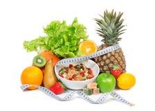 Diet weight loss breakfast concept with tape measure. Organic green apple, cereal bowl, orange juice, pineapple, muesli cereal bowl, pear, kiwi, lemon, rahat Stock Photos