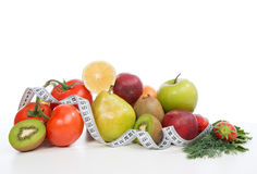 Diet weight loss breakfast concept with tape measure. Organic green apple,  tomatoes, strawberries, parsley, kiwi, grapefruit, pear  on a white background Stock Image