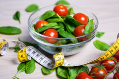 Diet and weight loss concept - salad with spinach and tomatoes a. Nd measure tape on wooden table background Royalty Free Stock Photography