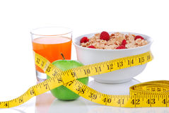 Diet weight loss concept with tape measure apple. Diet weight loss concept with tape measure natural green apple, corn healthy flakes with fresh raspberries and Royalty Free Stock Image