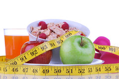Diet weight loss food breakfast concept. With tape measure natural green apple, corn healthy flakes with fresh raspberries and carrot juice on a white Royalty Free Stock Image
