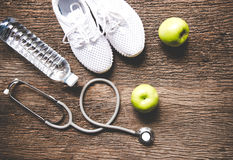 Diet and weight loss for healthy care with medical stethoscope, fitness equipment,fresh water and green apple on old wooden backgr royalty free stock photography