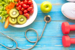 Diet and weight loss for healthy care with medical stethoscope, fitness equipment,measuring tap,fresh water and green apple on woo. Den background top view Royalty Free Stock Photos