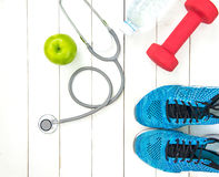 Diet and weight loss for healthy care with medical stethoscope, fitness equipment,measuring tap,fresh water and green apple on woo stock photos