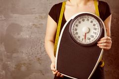 Diet and weight - young woman with a scale.  royalty free stock photo