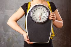 Diet and weight - young woman with a scale.  royalty free stock images