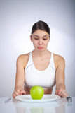Diet Woman. Woman looking dissapointed at a green apple on a plate Stock Photo