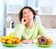 Free Diet. Woman Choosing Between Fruits And Sweets Stock Images - 26733814
