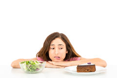 Diet woman deciding between cake and salad Royalty Free Stock Photo