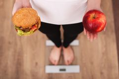 Diet. Woman Measuring Body Weight On Weighing Scale Holding Burger and apple. Sweets Are Unhealthy Junk Food. Dieting, Healthy Eat Stock Images