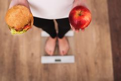 Diet. Woman Measuring Body Weight On Weighing Scale Holding Burger and apple. Sweets Are Unhealthy Junk Food. Dieting, Healthy Eat Stock Photo