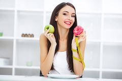 Diet. Woman Measuring Body Weight On Weighing Scale Holding Donu. T and apple. Sweets Are Unhealthy Junk Food. Dieting, Healthy Eating, Lifestyle. Weight Loss stock photo