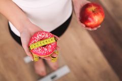 Diet. Woman Measuring Body Weight On Weighing Scale Holding Donut and apple. Sweets Are Unhealthy Junk Food. Dieting, Healthy Eati Royalty Free Stock Photography