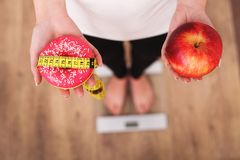 Diet. Woman Measuring Body Weight On Weighing Scale Holding Donut and apple. Sweets Are Unhealthy Junk Food. Dieting, Healthy Eati. Ng, Lifestyle. Weight Loss stock images