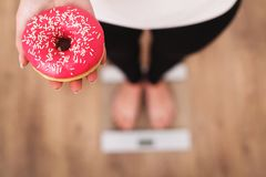 Diet. Woman Measuring Body Weight On Weighing Scale Holding Donut. Sweets Are Unhealthy Junk Food. Dieting, Healthy Eating, Lifest Royalty Free Stock Photos