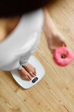 Diet. Woman On Weighing Scale, Holding Donut. Unhealthy Food. Ob Royalty Free Stock Image
