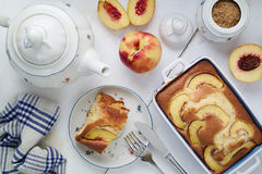 Diet yogurt sponge cake with peaches on table. Homebaked food. Concept of home-baked food. Diet yogurt sponge cake with peaches on table with tea pot, kitchen Stock Photo