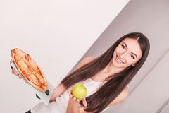 Diet. Young beautiful woman makes a choice between healthy lifes Stock Images
