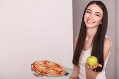 Diet. Young beautiful woman makes a choice between healthy lifes Stock Photos