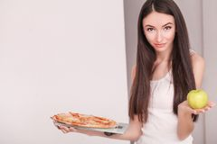 Diet. Young beautiful woman makes a choice between healthy lifes Royalty Free Stock Image