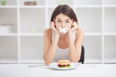 Diet. Young woman with duct tape over her mouth, preventing her. Young woman with duct tape over her mouth, preventing her to eat junk food. Healthy eating Stock Photo