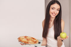 Diet. A young woman holding a pizza on the scales. The concept of healthy eating Royalty Free Stock Photo