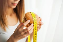 Diet. Young woman preventing her to eat junk food. Healthy eating concept royalty free stock image