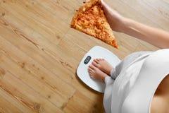 Dieta, alimentos de preparación rápida Mujer en la escala que sostiene la pizza obesidad Imagen de archivo
