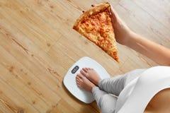 Dieta, alimentos de preparación rápida Mujer en la escala que sostiene la pizza obesidad Fotos de archivo libres de regalías