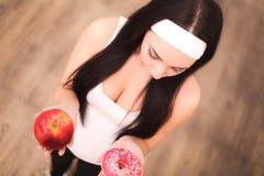 Dieta Conceito de dieta Alimento saudável Mulher nova bonita que escolhe entre frutas e doces Fotos de Stock