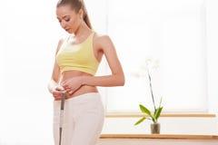 Dieta Conceito de dieta Mulher no sportswear que mede sua cintura fotografia de stock royalty free