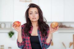 Dieta Concepto de dieta Alimento sano Mujer joven hermosa que elige entre las frutas y los dulces Pérdida de peso fotografía de archivo libre de regalías