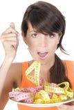 Dieta de la mujer que come un mesure de la cinta Fotos de archivo libres de regalías