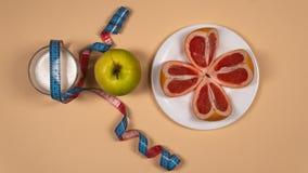 Dieta di concetto - alimento sano con la mela, il pompelmo, l'arachide, il yogurt e nastro adesivo di misurazione su fondo giallo fotografie stock