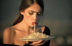 Dieta e alimento biológico saudável, Italia A mulher do cozinheiro chefe com bordos vermelhos come a massa Fome, apetite, receita fotografia de stock