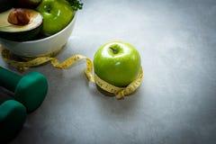 Dieta e conceito saudável da vida Medida da torneira maçã e da escala verdes do peso com legume fresco, imagens de stock royalty free